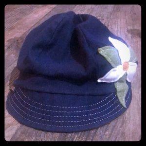 Blue denim hat with brim and flower.